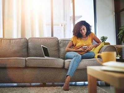 Equiniti 55917164917 Woman On Sofa With Phone Thumbnail Size